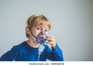 Boy making inhalation with a nebulizer at home.