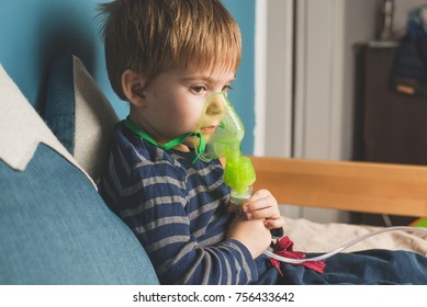 Boy making inhalation with nebulizer at home. child asthma inhaler inhalation nebulizer steam sick cough concept