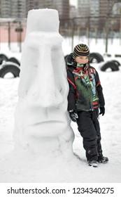 Boy making a winter snowman. An unusul snowman outdoors in snowy winter