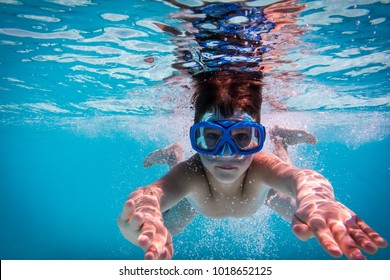 Boy in mask dive in swimming pool, underwater shoot