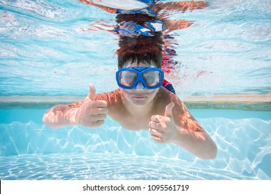 Boy in mask and flippers dive in swimming pool, showing the thumbs up sign, underwater shoot