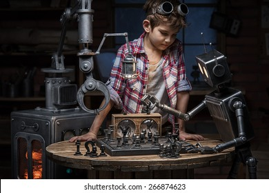 Boy mechanic looks like two robots play a game of chess in the studio in the evening