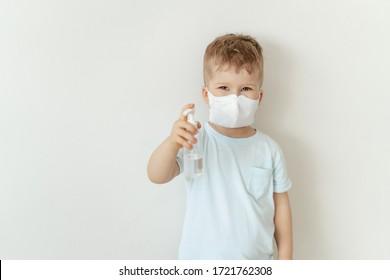Junge in der medizinischen Gesichtsmaske Hold Sanitiser Flasche. Kaukasisches Kind, das Grippe trägt, Blick auf die Kamera. Kleinkind mit Antiseptika, Sterilisationsel. Corona-Virus-Pandemie-Konzept
