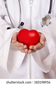 boy in a medical lab coat with a stethoscope, holding hands red heart