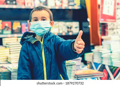 Boy in medical mask at bookstore. young boy chooses books in a bookshop. boy wear a protective mask In a bookstore. Concept of life And protect yourself from the coronavirus outbreak. toned