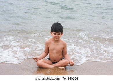Boy meditating on the beach with eyes closed