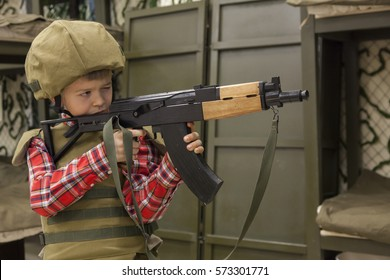 boy in military uniform learning to fire a gun