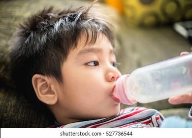 The boy with a milk bottle. Close up the boy wit a mink bottle.