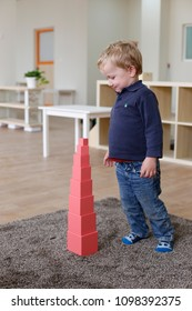 Boy in a montessori classroom with pink tower