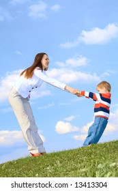 Boy with mother playing on grass at blue sky background