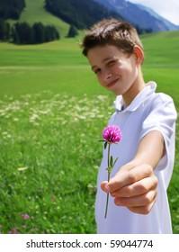 Boy in mountainous environment giving wild flower.