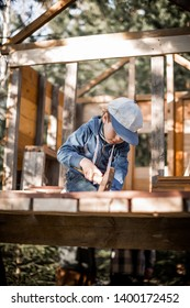 A boy is nailing building a tree house. Image with selective focus and toning