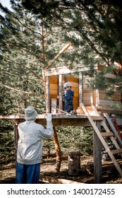 A boy is nailing building a tree house and his grandfather is helping him. Image with selective focus and toning