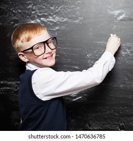 Boy near blackboard. Child at school. Student at classroom