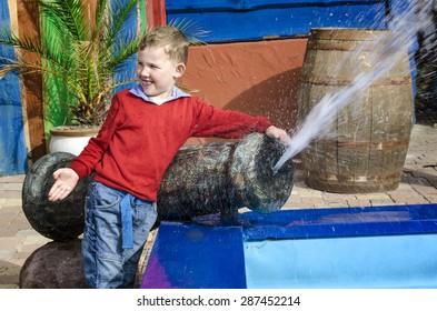 The boy near the fountain sprays water.