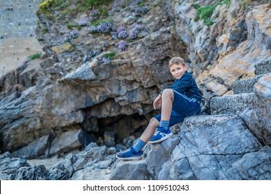 Boy near the rock at seaside, Tenby, Wales
