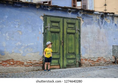 a boy near a vitage green door of a old blue building