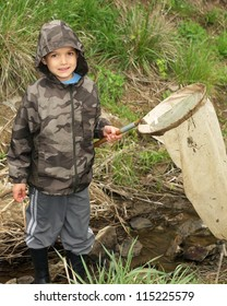 Boy with net and rain boots catching animals in a stream