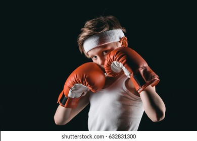 boy obscuring face with boxing gloves isolated on black, active kids concept