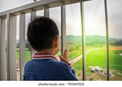 The boy observes the world through the bars of the tower.