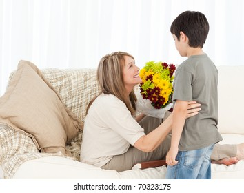 Boy offering flowers to his grandmother at home