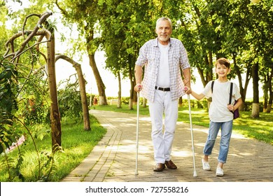 A boy and an old man on stilts for adults are walking in the park. The boy is holding the old man's hand. They are happy