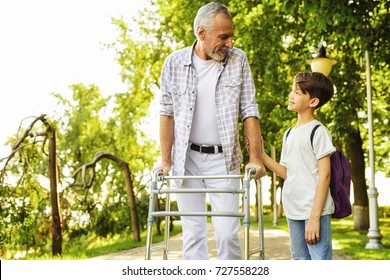 A boy and an old man on stilts for adults are walking in the park. A boy with a backpack behind him comes alongside the old man