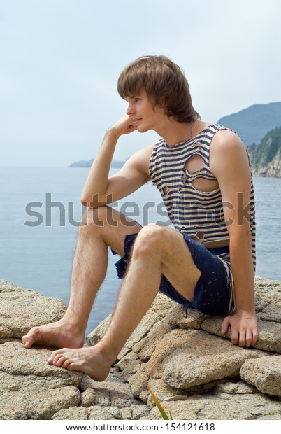 The boy in old stripped vest is sitting on rocks at sea.
