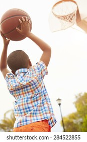 Boy On Basketball Court Shooting For Basket