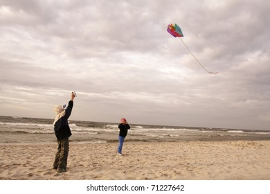 Boy on beach playing with a kite