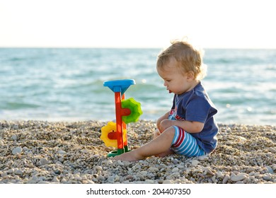 boy on the beach playing with toy
