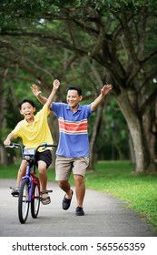 Boy on bicycle, father behind him, both with arms outstretched