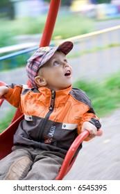 Boy on carousel at amusement park. Motion