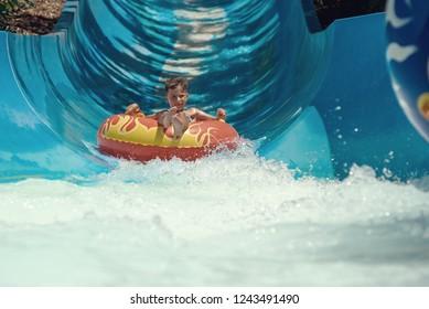 Boy on floater sliding down slide in waterpark.
