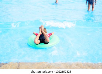 A boy on green life ring at the water park.Happy time for children.