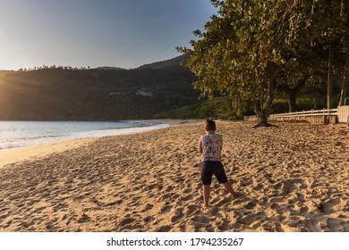Boy on his back watching the sunny Toque-Toque beach. Sun lighting the Praia de Toque-Toque São Sebastião, on the coast of São Paulo.