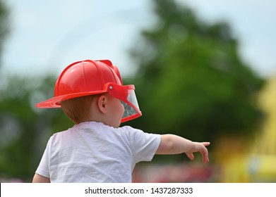 A boy on his father's shoulder is wearing a red firefighter helmet while pointing at someone with his right hand.