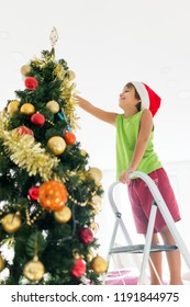 Boy on ladder decorating tree for Christmas