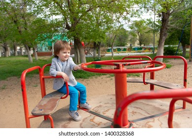 boy on the playground rides on a swing