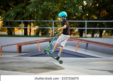 A boy on a scooter and in protective helmet do incredible stunts in skate park. Extreme jump. The concept of a healthy lifestyle and sports leisure