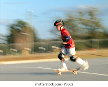 Boy on skateboard getting ready to do an Ollie.  Shot with a slow shutter speed.