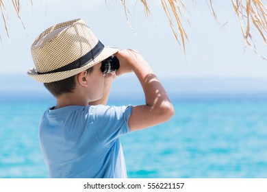Boy on summer tropical beach with binoculars