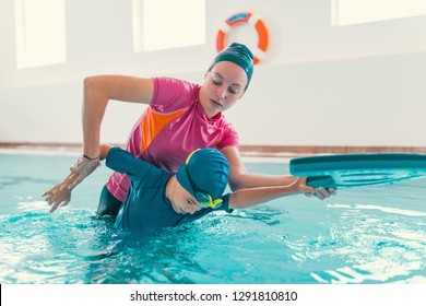 Boy on swimming class with instructor