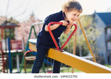 Boy on the teeter at playground. Kid playing outdoor.