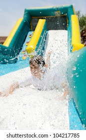 Boy on Water Slide. Boy making a splash as he slides down a water slide.