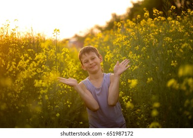 Boy on a yellow rapeseed field in the evening at sunset.