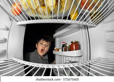 boy open the door and looking in refrigerator