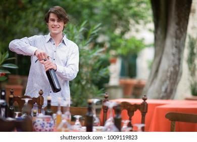 Boy opening wine