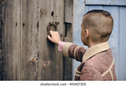 boy opens the door to the old house