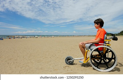 boy with orange t-shirt sitting on the special wheelchair with aluminum alloy wheels to move on the beach